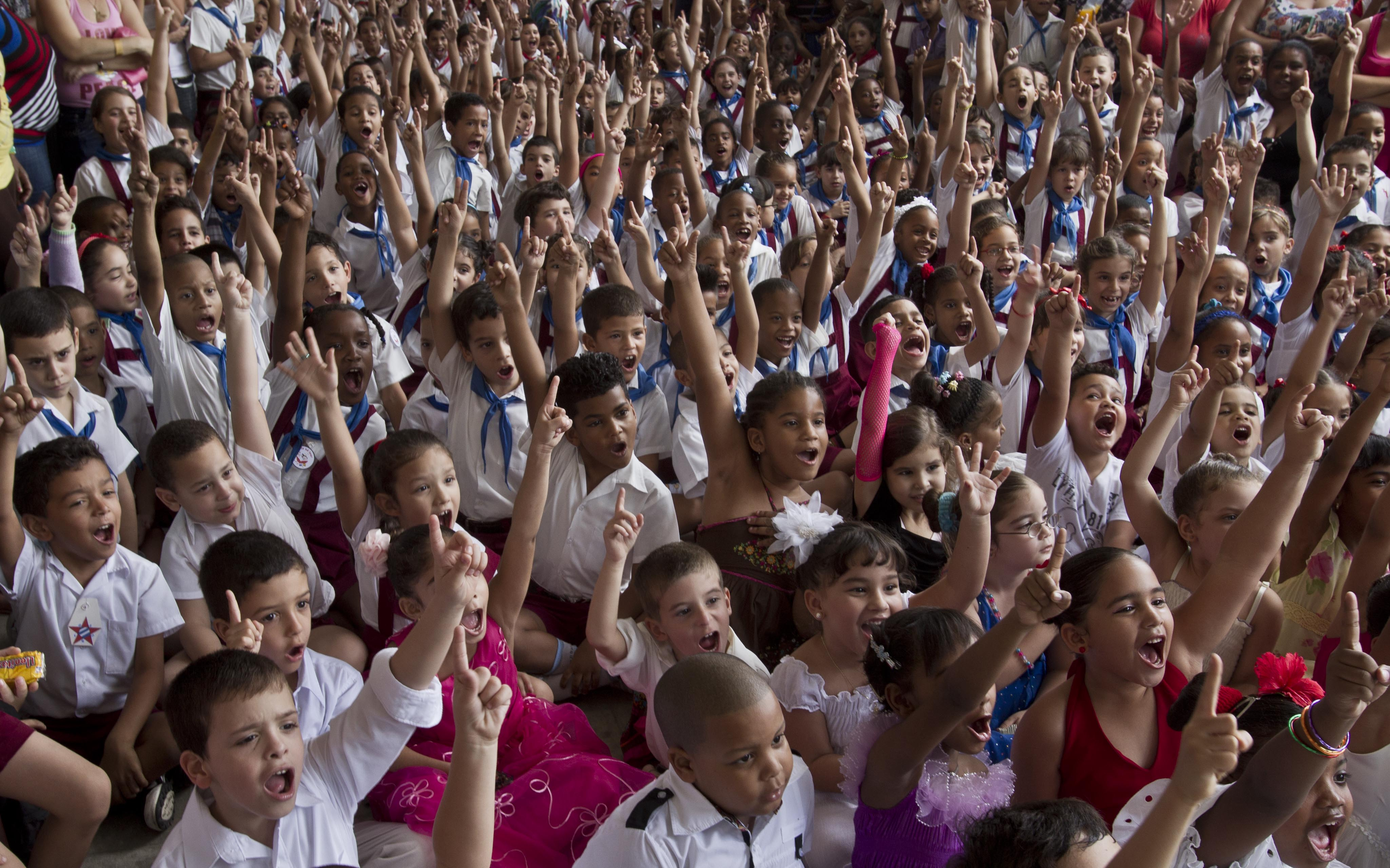"Young students cheer during a celebration to mark the anniversaries of the Organization of Cuban Pioneers and of the Union of Communist Youth at the Angela Landa elementary school in Old Havana, Cuba, Friday, April 4, 2014. Cuban schoolchildren are referred to as ""pioneers,"" and the organization was founded in 1961 to encourage the values of education and social responsibility among children and adolescents. (AP Photo/Franklin Reyes) ORG XMIT: XFR105"